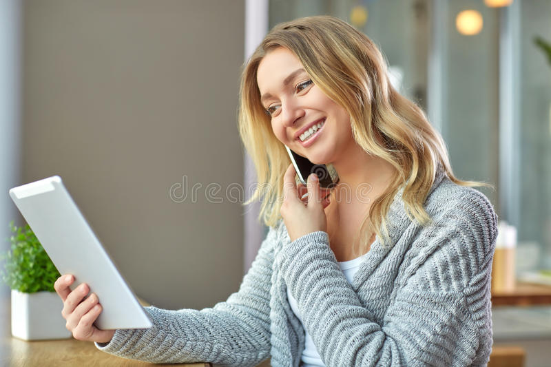 Beautiful young woman holding laptop and talking on the phone at the cafe. Business royalty free stock photo