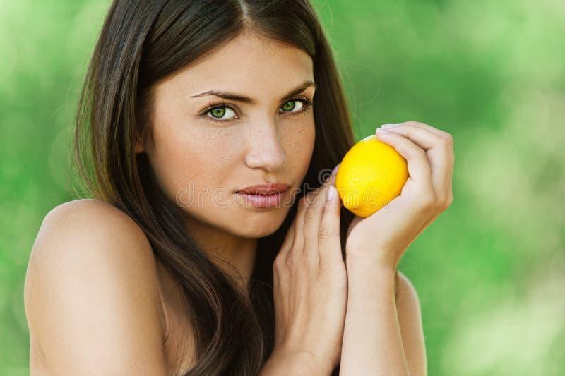 Beautiful young woman holding lemon royalty free stock photography