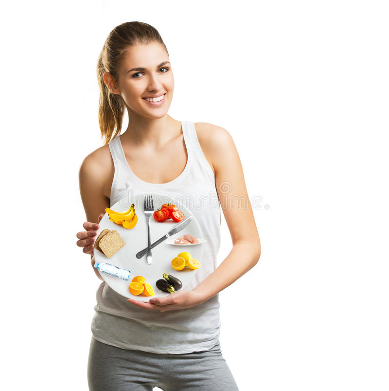 Beautiful young woman holding a plate with food, diet concept. Beautiful young woman holding a plate with food, diet and time concept royalty free stock photo