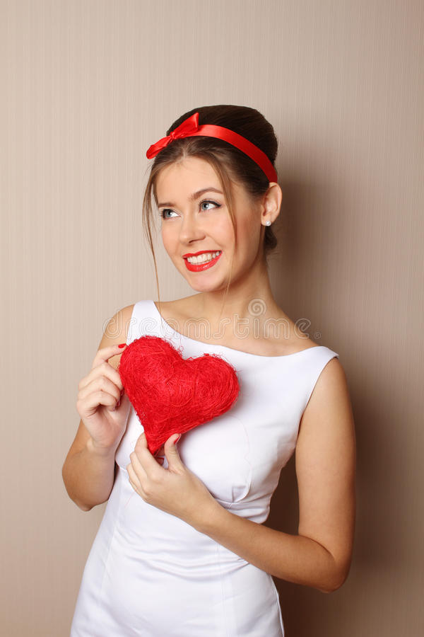 Beautiful young woman holding a red heart stock image