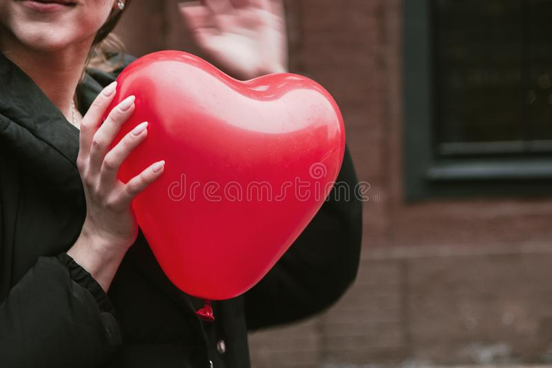 Beautiful young woman holding a red heart shaped ball, Valentine`s Day.  stock images