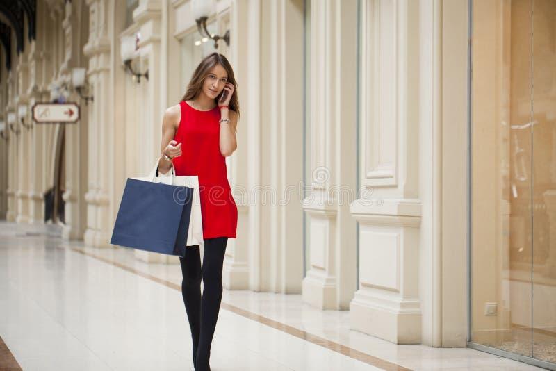 Beautiful young woman holding shopping bags walking in the shop stock image