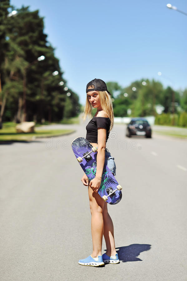 Beautiful young woman holding a skateboard royalty free stock photos