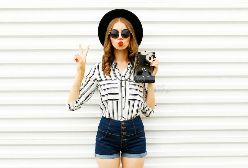 Beautiful young woman holding vintage film camera, sending sweet air kiss in black round hat, shorts, white striped shirt on white royalty free stock photography