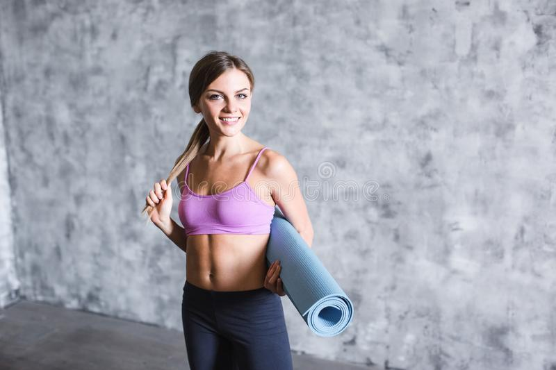 Beautiful young woman is holding a yoga mat looking at camera and smiling on a gray background stock photos