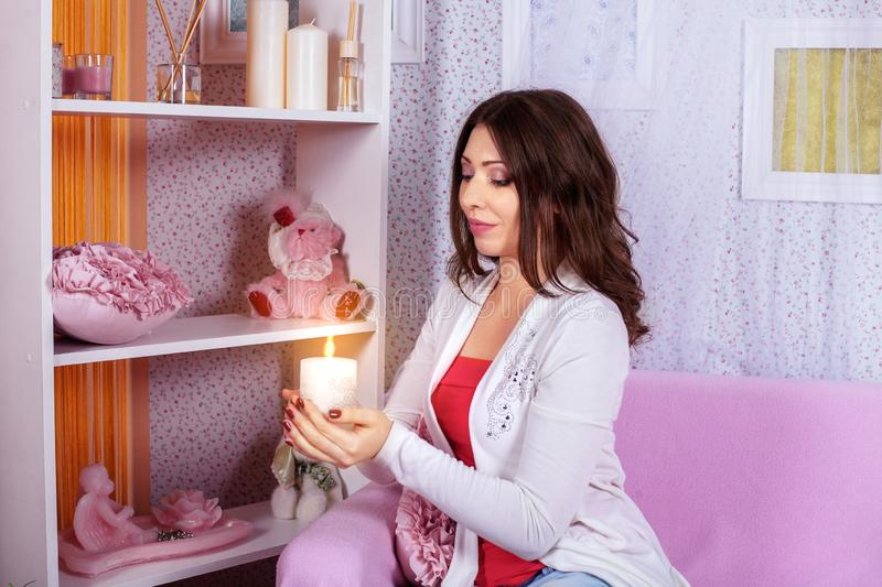 A beautiful young woman holds a candle in a pink room. The concept of lifestyle stock images