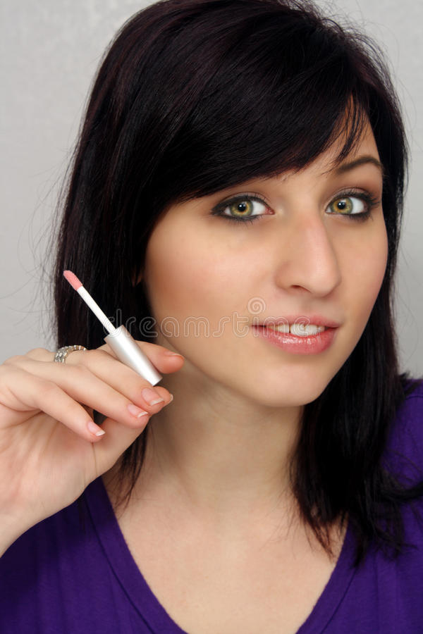 Beautiful Young Woman Holds a Cosmetics Applicator. A lovely young woman holds a lipstick or lip gloss applicator similar to the way a cigarette is commonly held stock photos