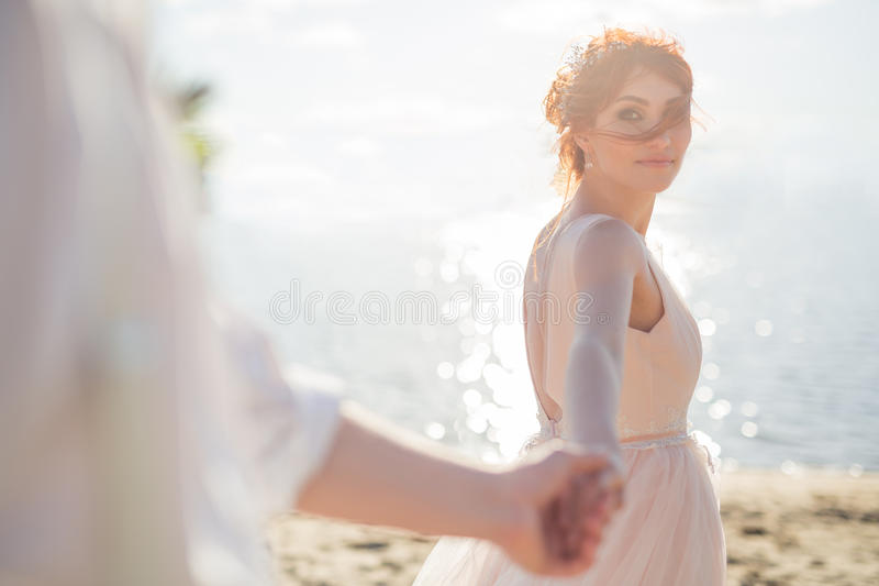A beautiful young woman,holds the hand of the man in the open air. Follow me. The haze is created for romantic frame. stock photography