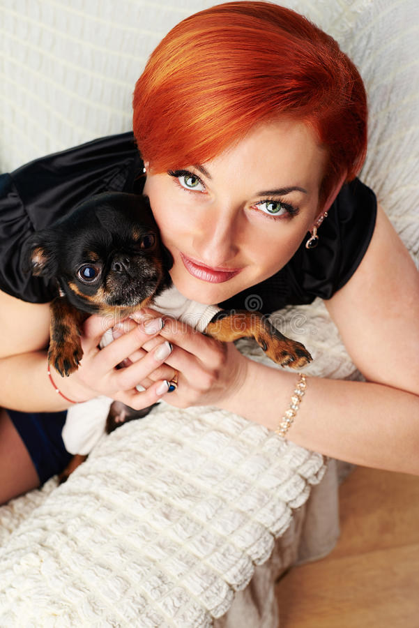 Beautiful young woman holds her dog in her arms stock photo