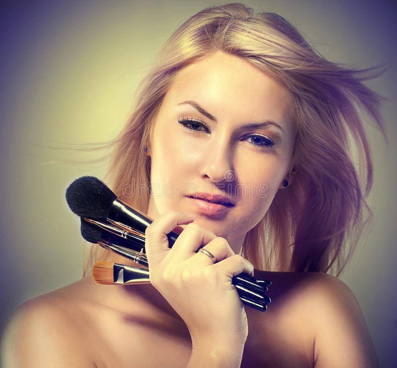 Beautiful young woman holds the make-up brushes stock photography
