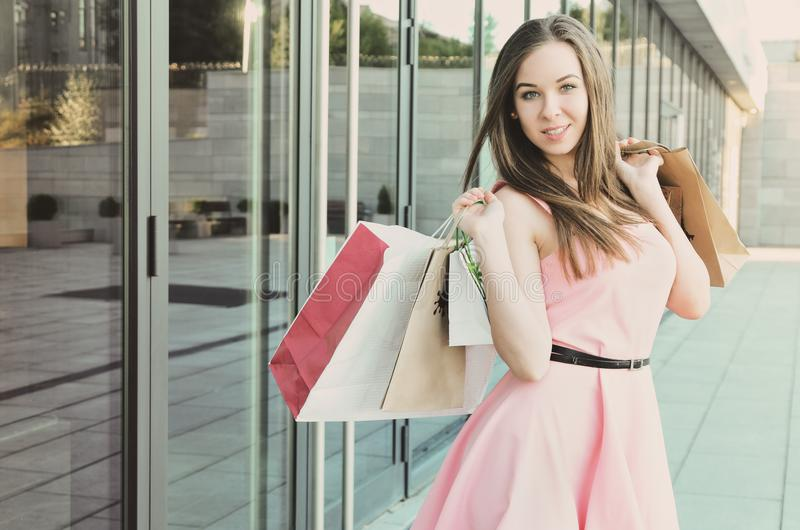 A beautiful young woman holds paper bags in her hands royalty free stock photography