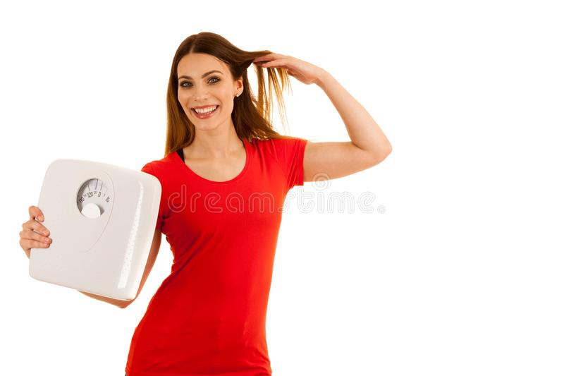 Beautiful young woman holds scale as a sign of weightloss isolated over white background stock image