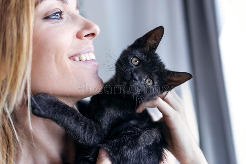 Beautiful young woman at home holding and hug her lovely fluffy cat stock image