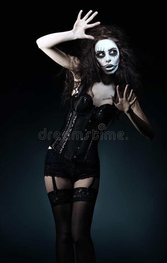 Beautiful young woman in the image of sad gothic freak clown. Beautiful young woman in the image of a sad gothic freak clown royalty free stock image