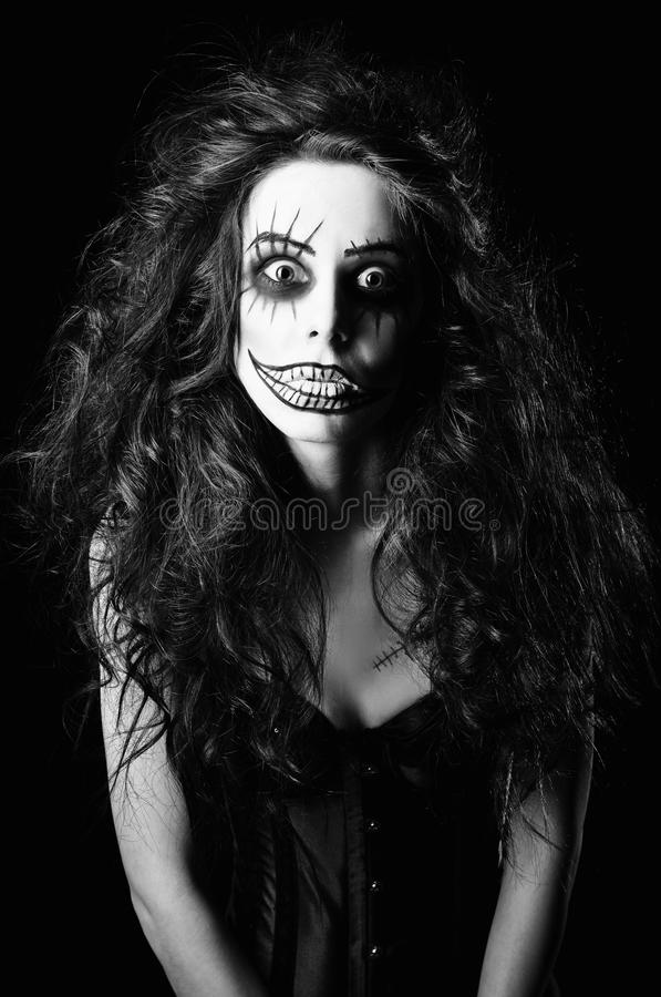 Beautiful young woman in the image of sad gothic freak clown. Black and white. Beautiful young woman in the image of a sad gothic freak clown. Black and white royalty free stock photo