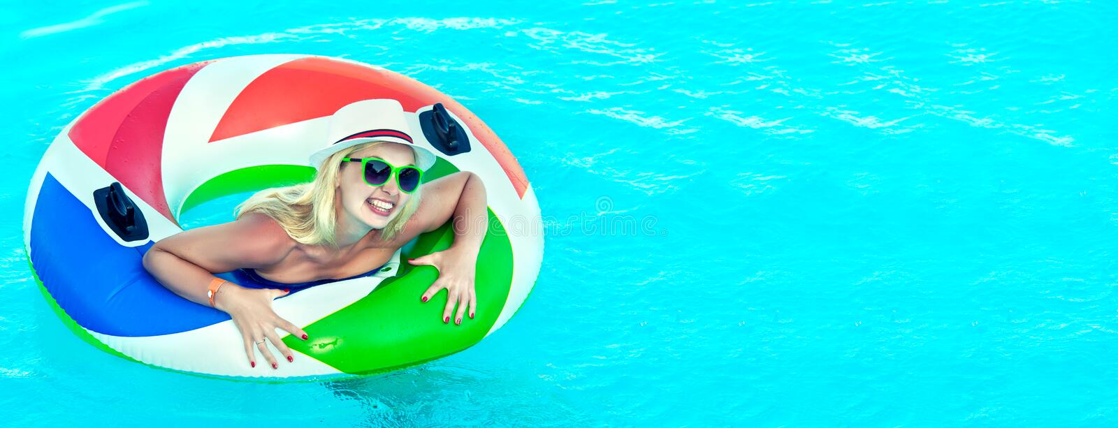 Beautiful young woman with inflatable ring relaxing in blue swimming pool royalty free stock images