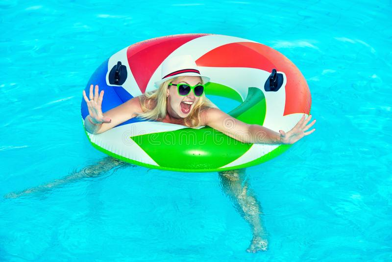 Beautiful young woman with inflatable ring relaxing in blue swimming pool stock photo
