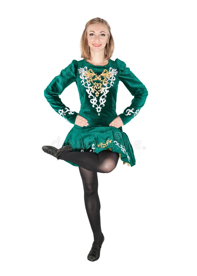 Beautiful young woman in Irish dance green dress jumping isolate. D on white stock photography