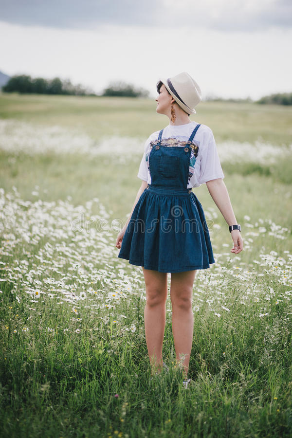 Beautiful young woman in a jeans dress and straw hat posing in a camomile field royalty free stock photos