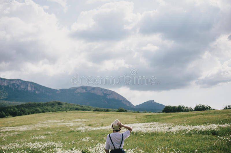 Beautiful young woman in a jeans dress and straw hat posing in a camomile field royalty free stock image