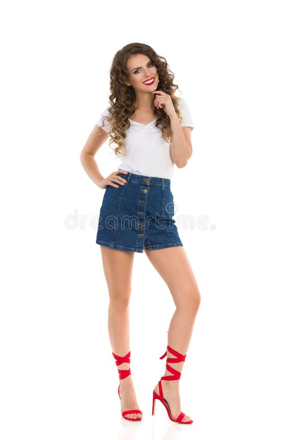 Young Woman In Jeans Mini Skirt And Red High Heels Is Standing, Holding Hand On Chin And Smiling. Beautiful young woman in jeans mini skirt, white top and red stock image