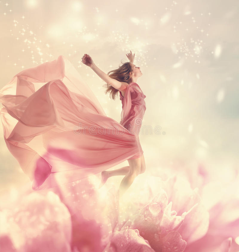 Beautiful young woman jumping on giant flower. Beautiful young woman jumping on a giant flower royalty free stock photos