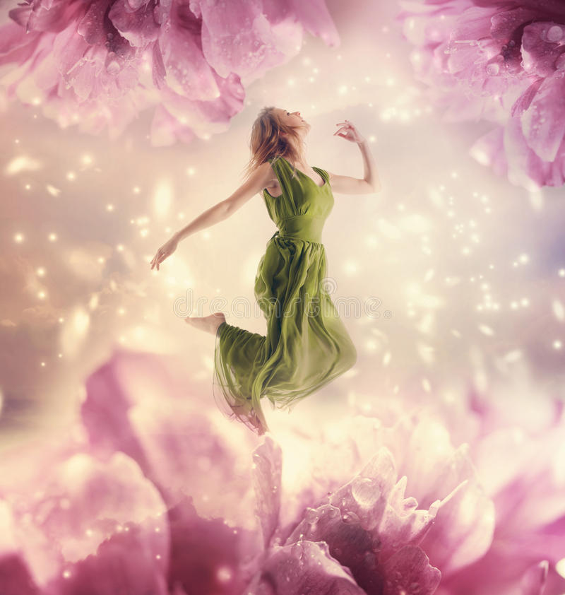 Beautiful young woman jumping on giant flower stock photos