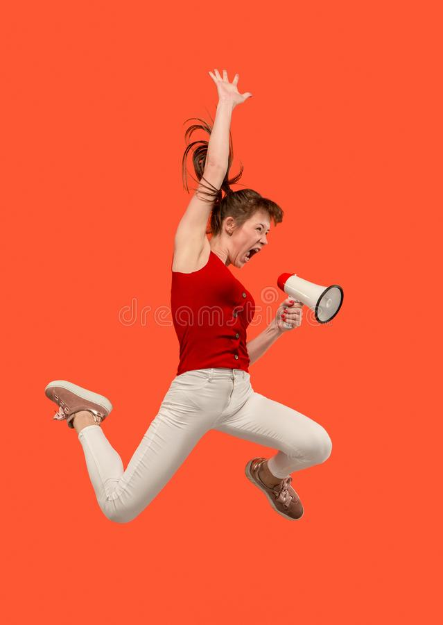 Beautiful young woman jumping with megaphone isolated over red background stock image