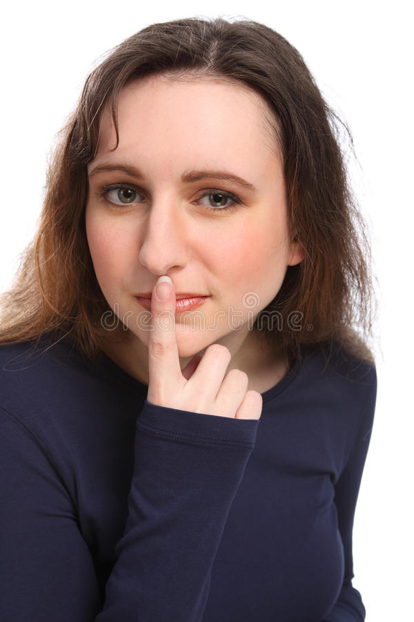 Beautiful young woman keeps secret finger on lips stock image