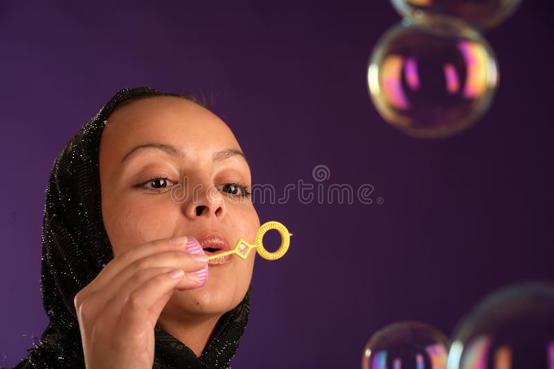 Beautiful Young Woman In Kerchief Blowing Bubbles Stock Photography