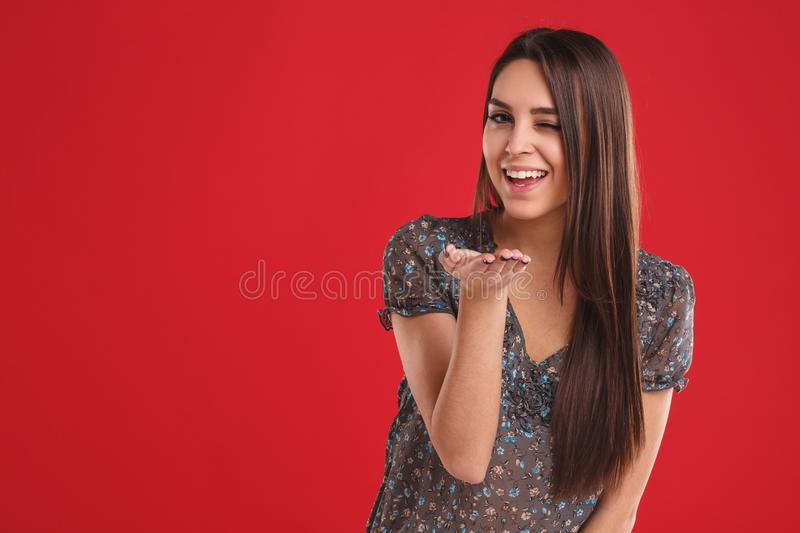 Beautiful young woman with kiss gesture. Portrait of a flirting girl. royalty free stock photo