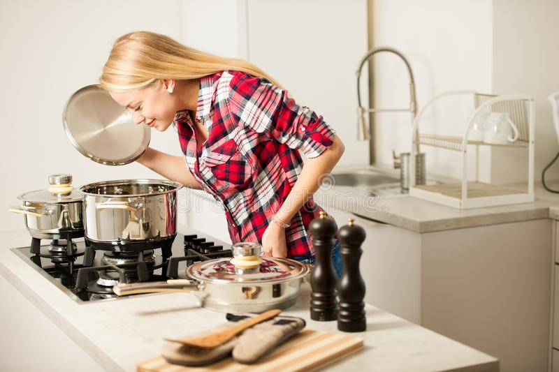 Beautiful young woman in kitchen cooks a delicious meal stock photography