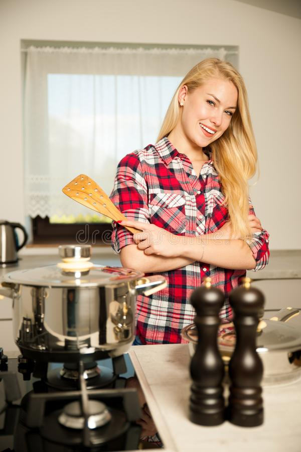 Beautiful young woman in kitchen cooks a delicious meal royalty free stock image