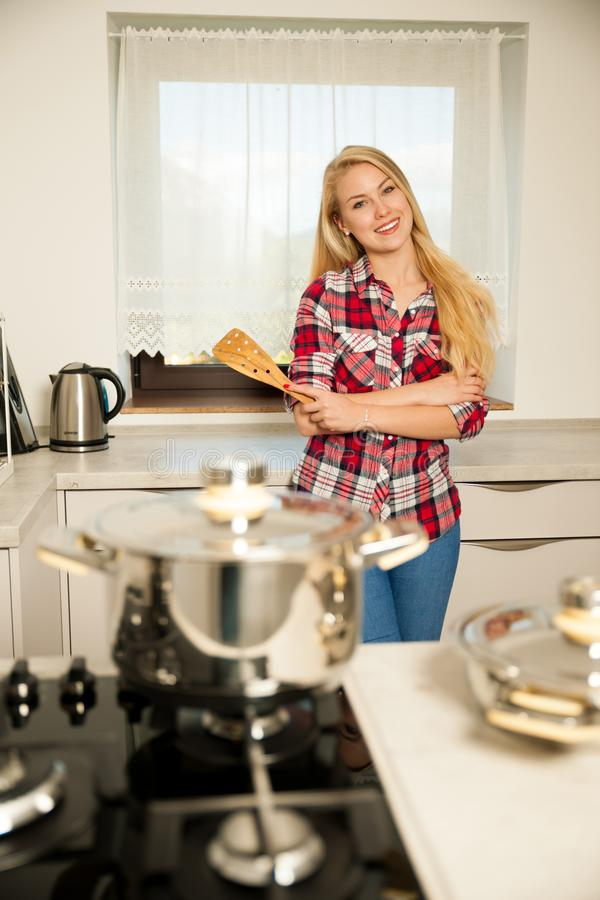 Beautiful young woman in kitchen cooks a delicious meal royalty free stock photos