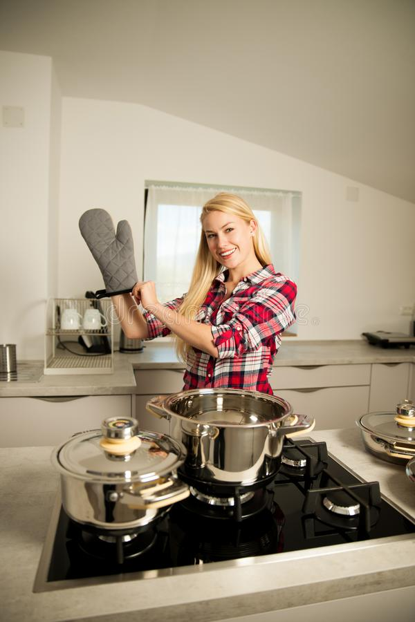 Beautiful young woman in kitchen cooks a delicious meal stock images
