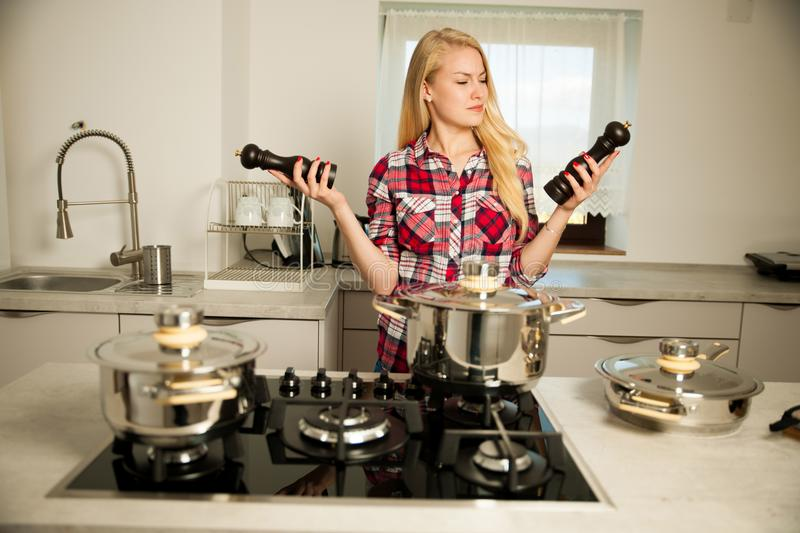 Beautiful young woman in kitchen cooks a delicious meal uncertain which spice to use royalty free stock images