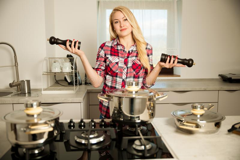 Beautiful young woman in kitchen cooks a delicious meal uncertain which spice to use royalty free stock photography