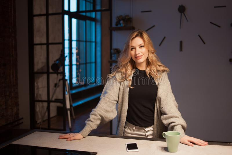 Beautiful young woman in the kitchen, early morning, dark in the apartment. stock photography