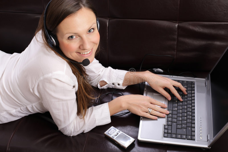 Beautiful young woman with laptop, cell phone and. Beautiful young smiling woman with laptop, cell phone and headset on the sofa stock images