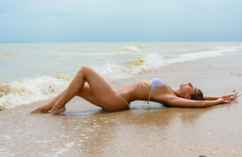 Beautiful young woman laying in the sea coast royalty free stock photo