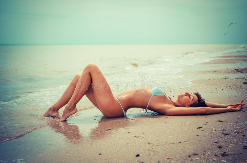 Beautiful young woman laying in the sea coast - with toning royalty free stock image