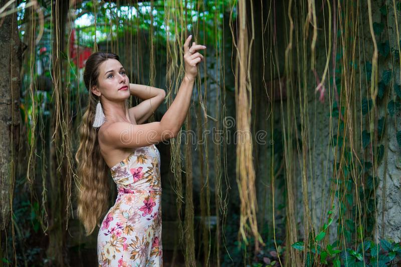 Beautiful young woman is leaning against a tree in the rain forest wearing sexy dress stock images