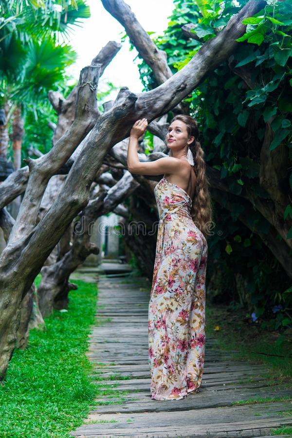 Beautiful young woman is leaning against a tree in the rain forest wearing sexy dress stock photo
