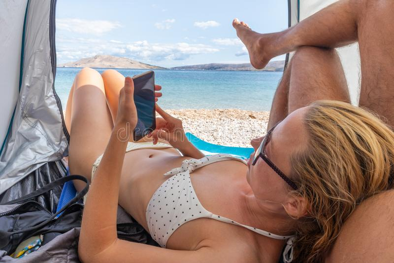 Beautiful young woman leaning on her partner while reading on her mobile phone, resting on the beach together and stock image