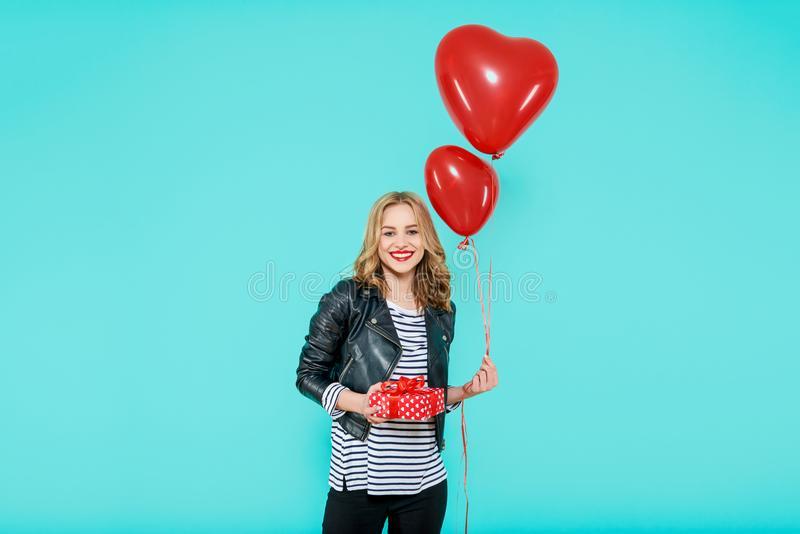 Beautiful young woman in leather jacket holding heart shaped balloons and wrapped birthday present. Valentine`s day concept. stock photography