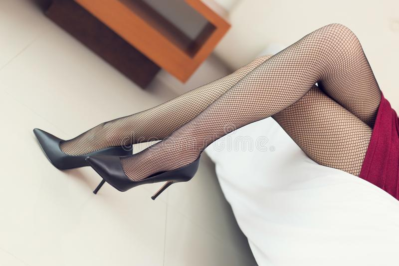 Beautiful young woman legs. In stocking - on white bed royalty free stock photography