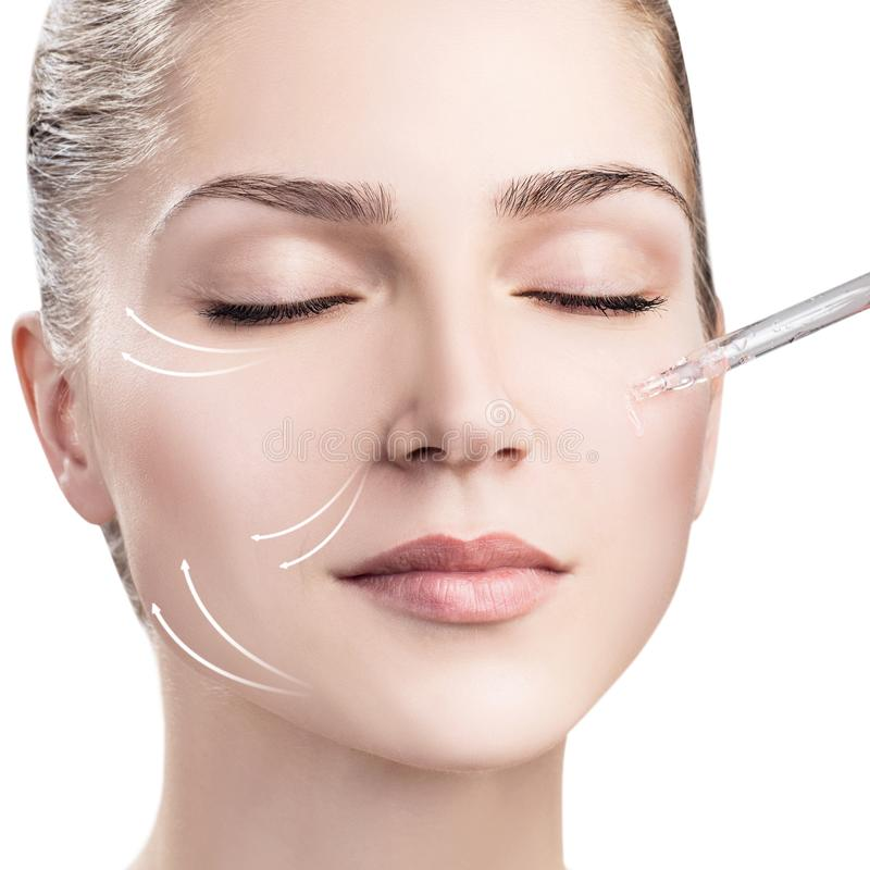 Woman`s face with lifting arrows and cosmetics oil stock photos