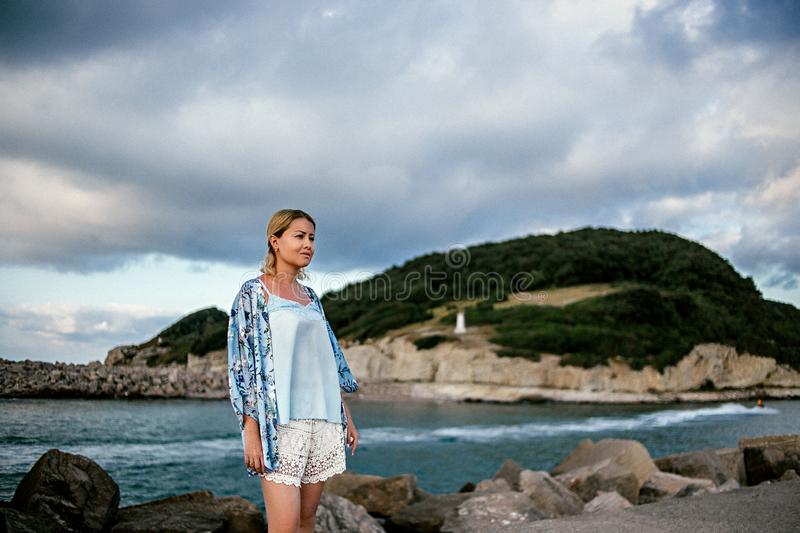 Beautiful young woman in light summer clothes by the sea. in the background mountains and beautiful sky royalty free stock image