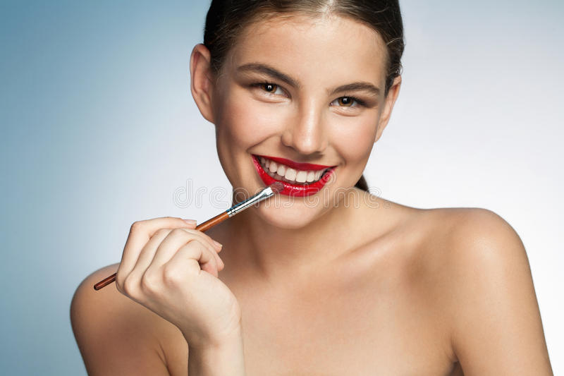 Beautiful young woman with lip brush royalty free stock photo