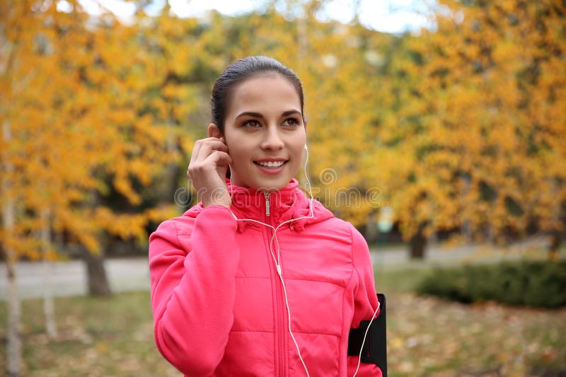 Beautiful young woman listening music in park royalty free stock images